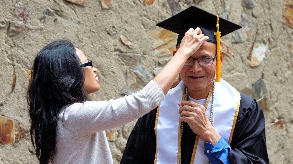 Eleonor Castillo adjusts her father's cap at a reception at Sacramento State, honoring students who completed their bachelor's degree through a long-distance program. (College of Continuing Education/Risa Knight)