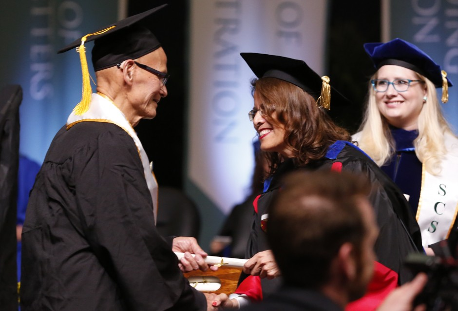 Rodolfo Castillo meets Professor Caroline Turner, Administrator-in-Charge, College of Education, as he walks through the commencement line and accepts his bachelor's degree. (Sacramento State/Jessica Vernone)