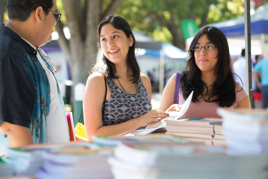 Siblings Jose Jauregui, a student at Sierra College, and Betsy and Cinthya Jauregui, students at Rocklin High, browse the free book fair during the Feria. (Sacramento State/Jessica Vernone)