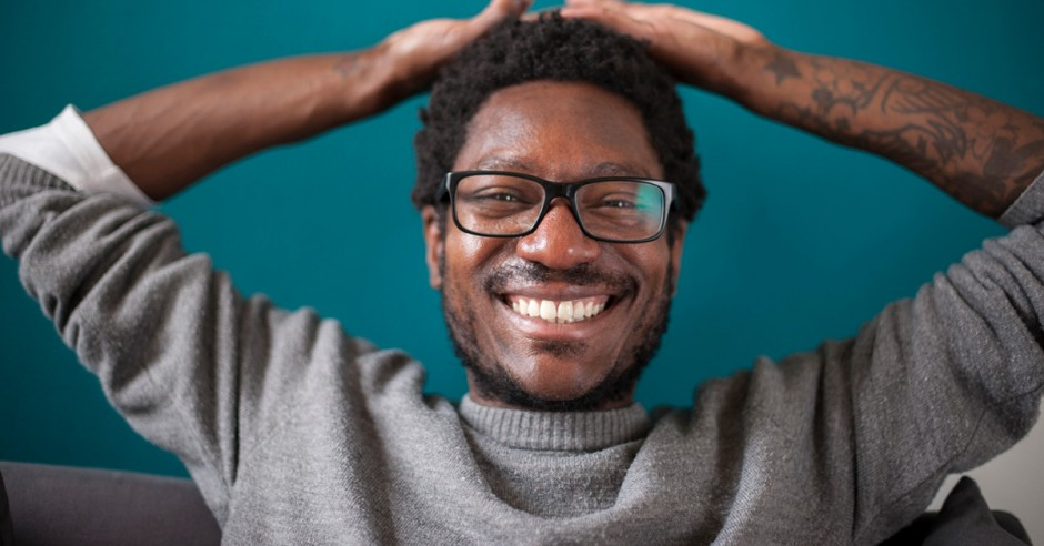 Man smiling with arms over his head